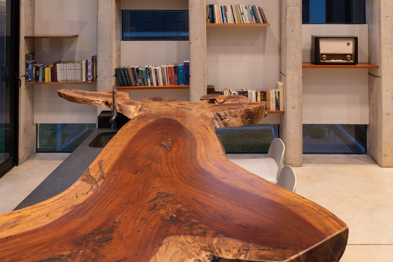 large live edge wood table with bookshelves in the background