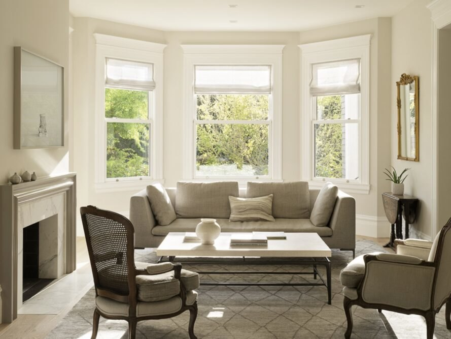 beige living room with beige sofa and two chairs near three windows