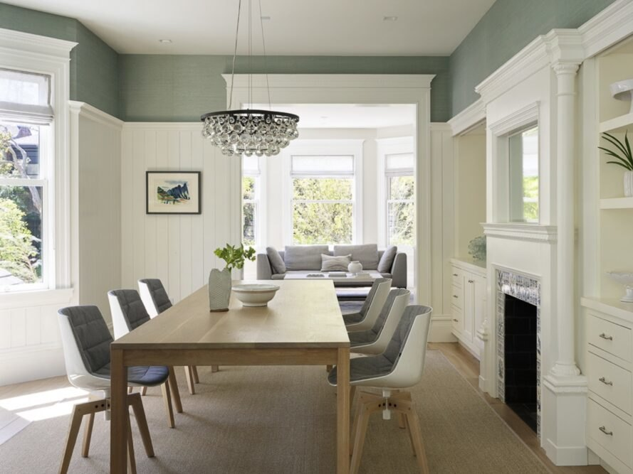 wood dining table with gray chairs in room with sage green and white walls