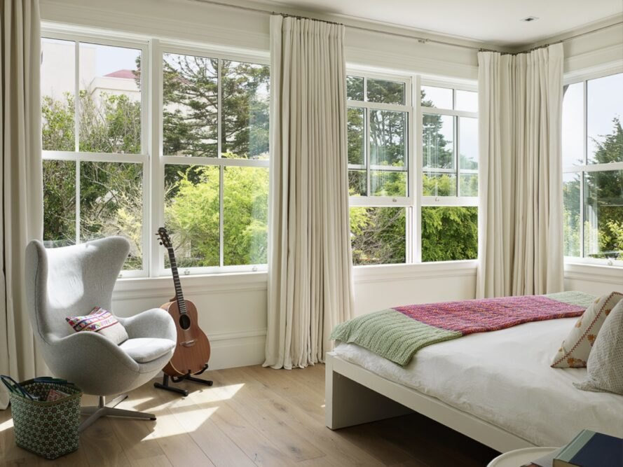 large white bed facing massive windows with views of trees