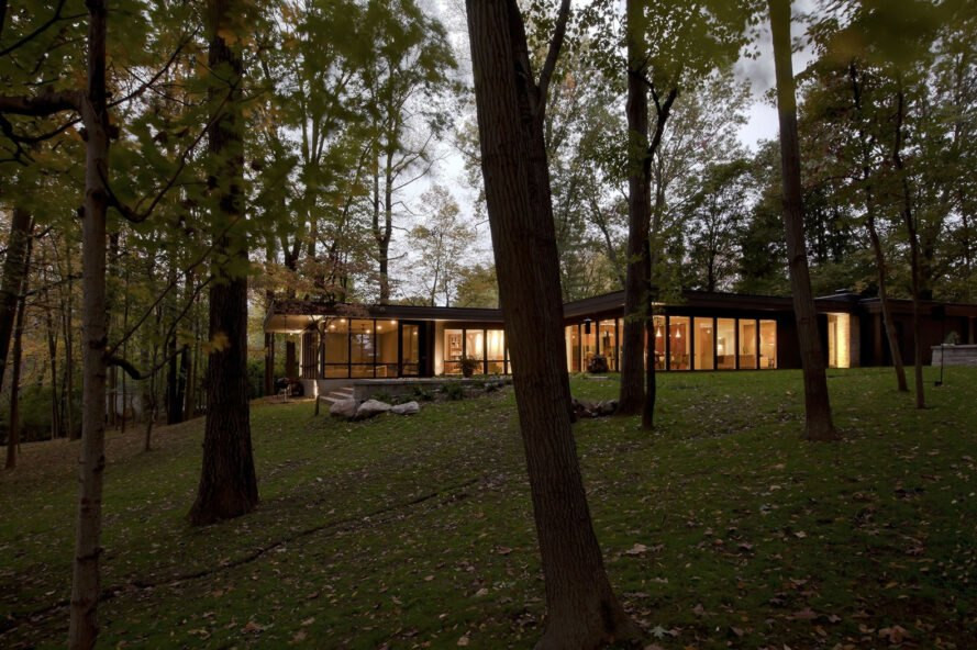 a house with floor-to-ceiling window walls in the middle of a forest