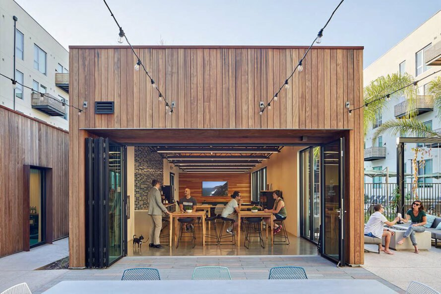 a wood paneled building with people sitting at tables inside