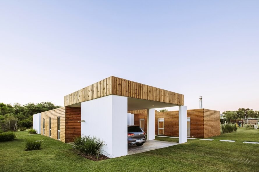 white and wood home with modern car port