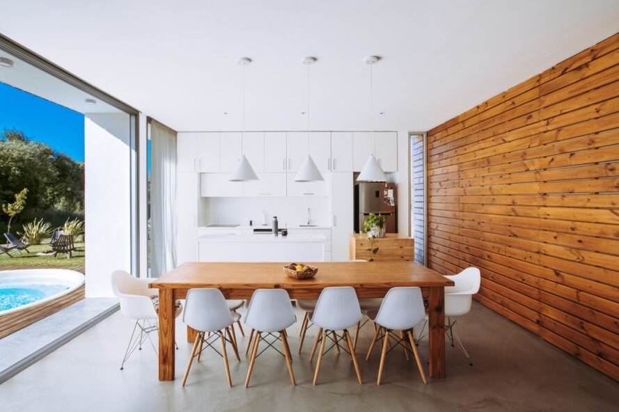 wood dining table with white chairs near white kitchen