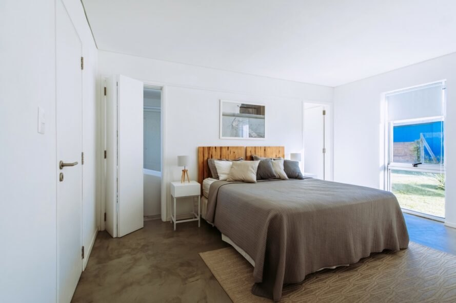 brown bed with wood headboard in white bedroom
