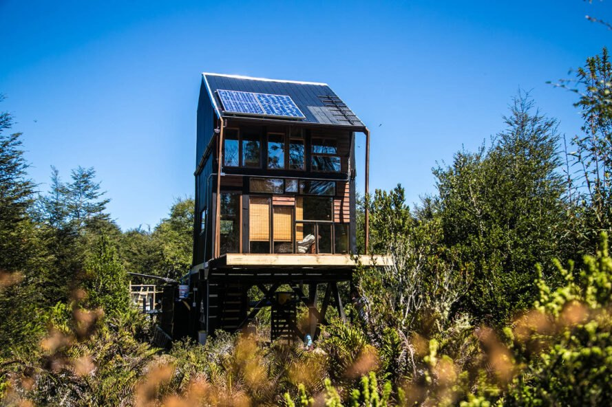 greenery surrounds a solitary cabin with several windows on the front facade and solar panels on the roof