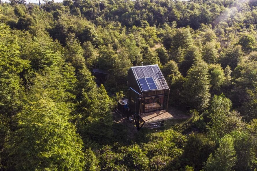 bright green trees surround a small, solitary cabin with a wood deck and solar panels on the roof