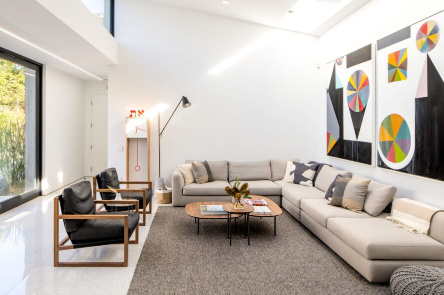 white sectional sofa and dark leather chairs in white living room
