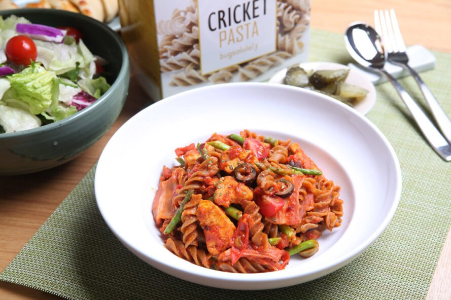 "to the left a salad, in the center a bow of pasta in red sauce. behind the bowl is a box that reads ""Cricket Pasta"""