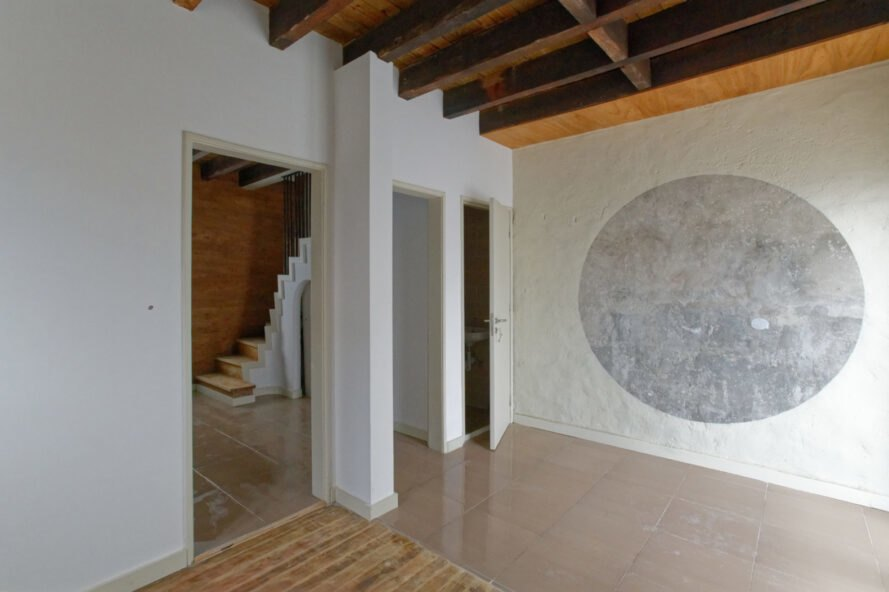 white room with gray round mural on wall