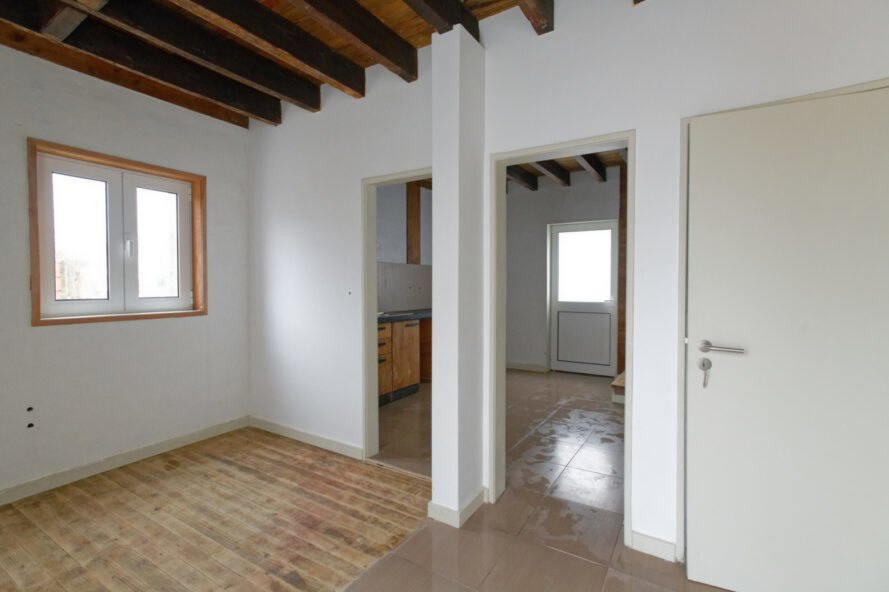 white room with two open doorways leading to other white rooms with wood ceiling beams