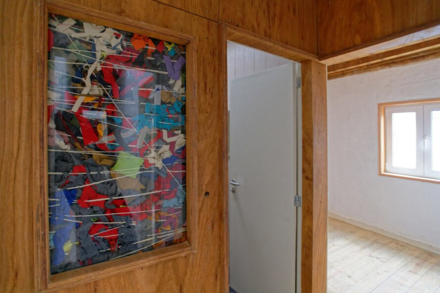 wood wall with glass panel revealing cloth insulation