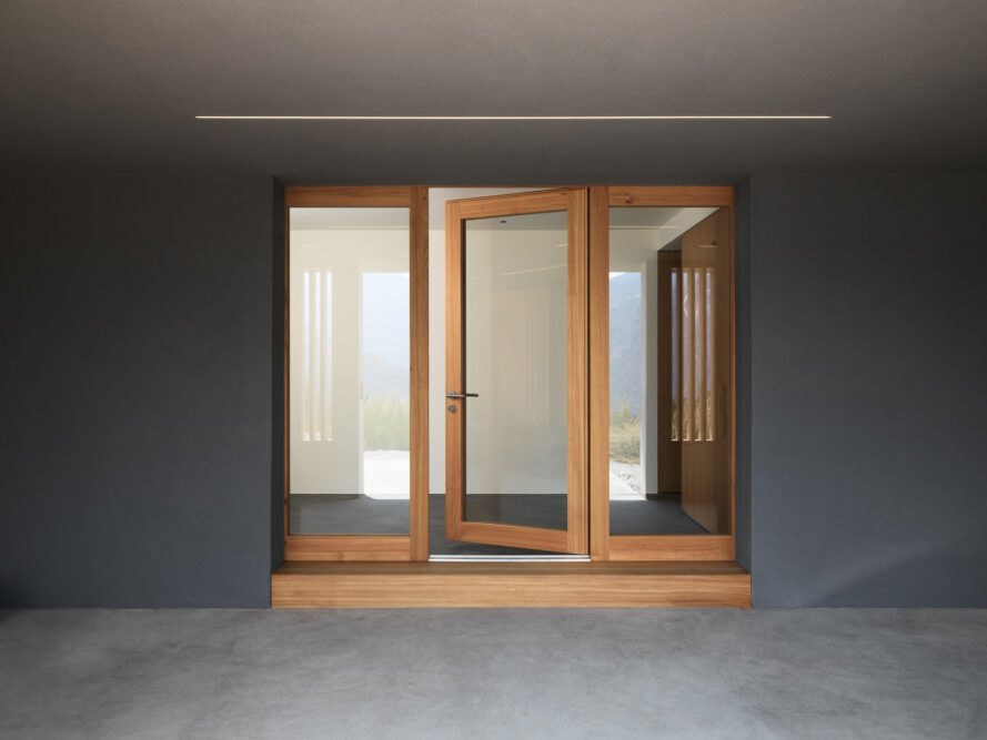 timber-framed glass doors on a concrete wall