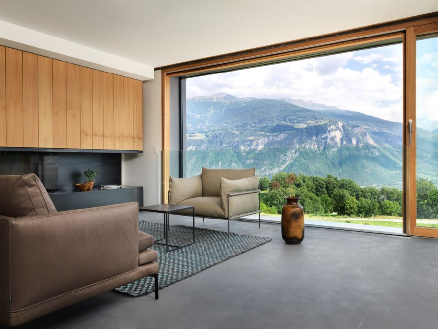 living area with beige sofa and chair and a glass wall framing mountainous views