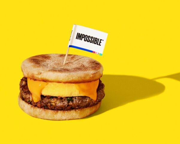 breakfast sandwich with plant-based sausage on yellow background