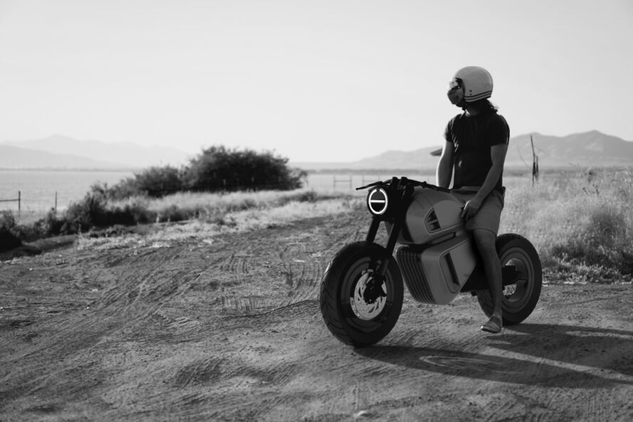 black and white photo of person riding a hybrid motorcycle