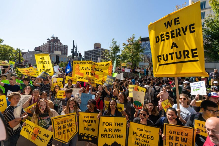 people holding yellow signs at a climate strike