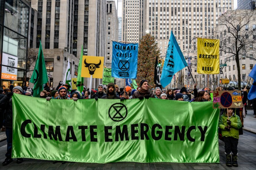 "crowd of protesters holding green sign that reads, ""Climate Emergency"""