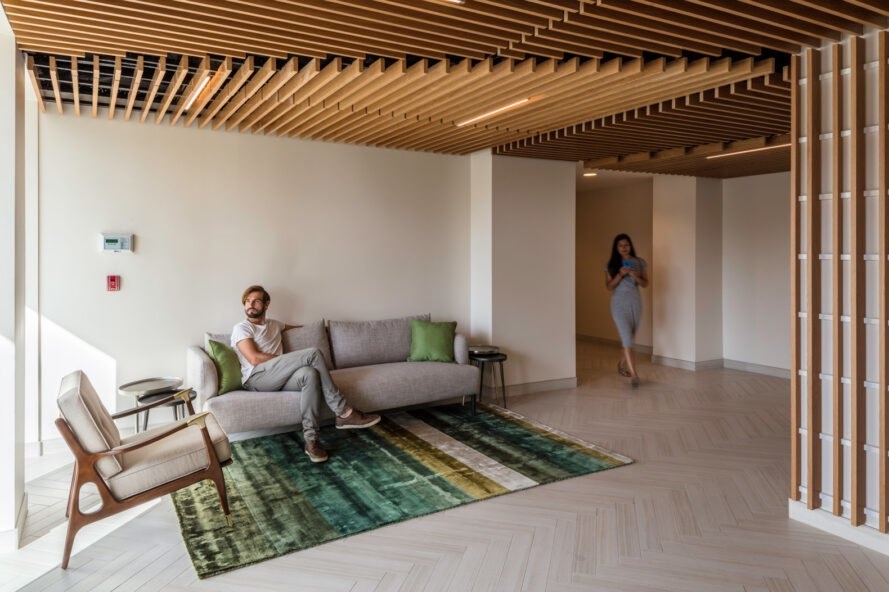 person sitting on gray sofa in apartment room with wood ceilings