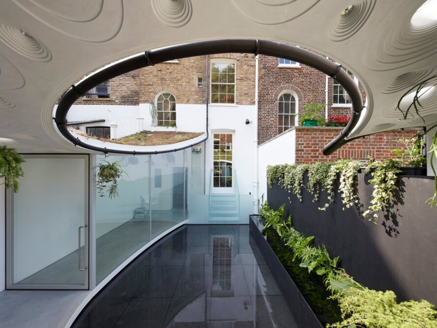 a white front door with brick around it, and a circular cut-out rooftop above.