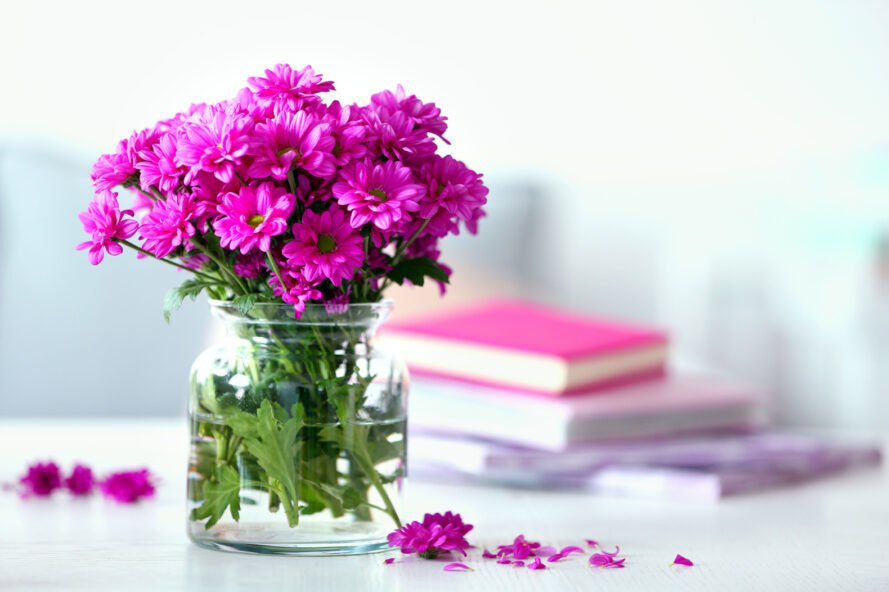 glass vase of pink flowers on white table