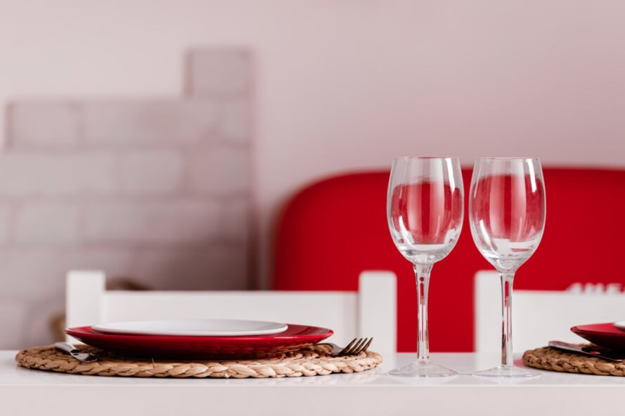 red and white plates and wine glasses set for dinner for two at a home dining table