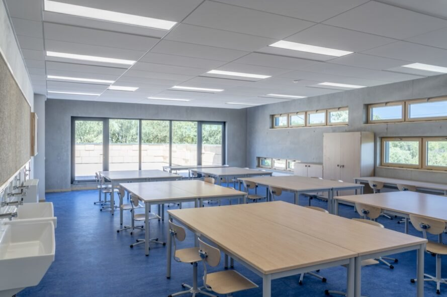 classroom with wood desks and blue floors