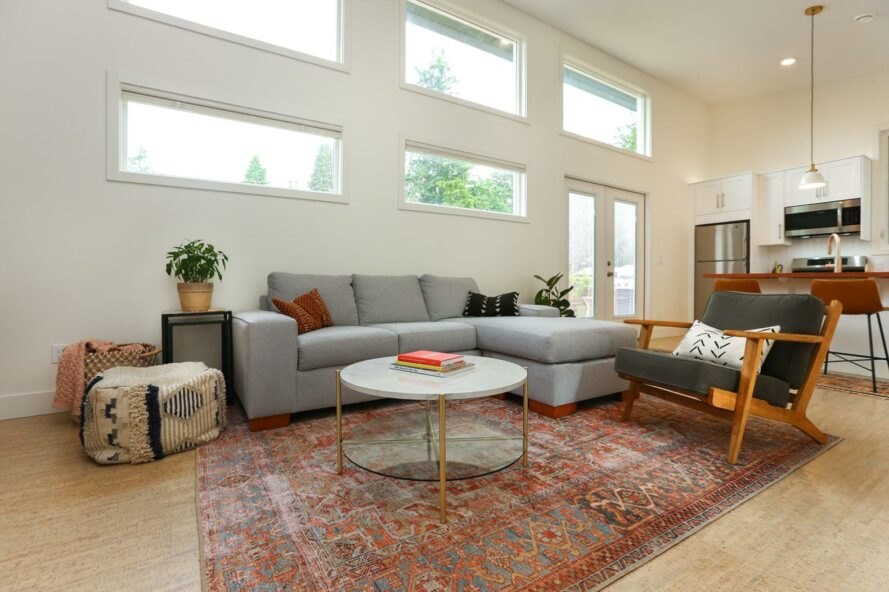 gray sofa, round coffee table and red patterned rug