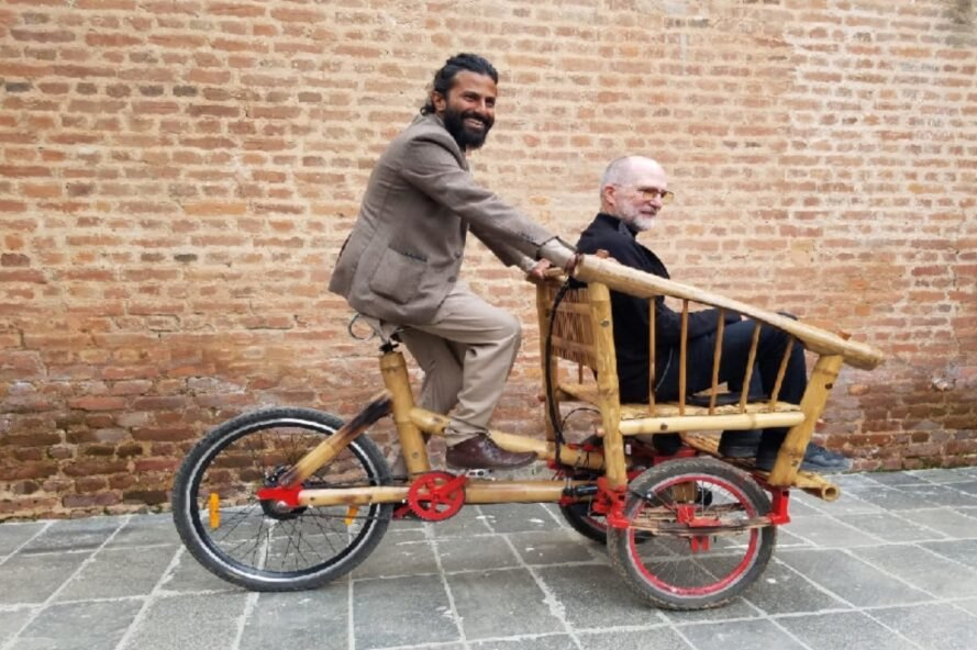 person in suit riding a bamboo bike with another person seated in the front
