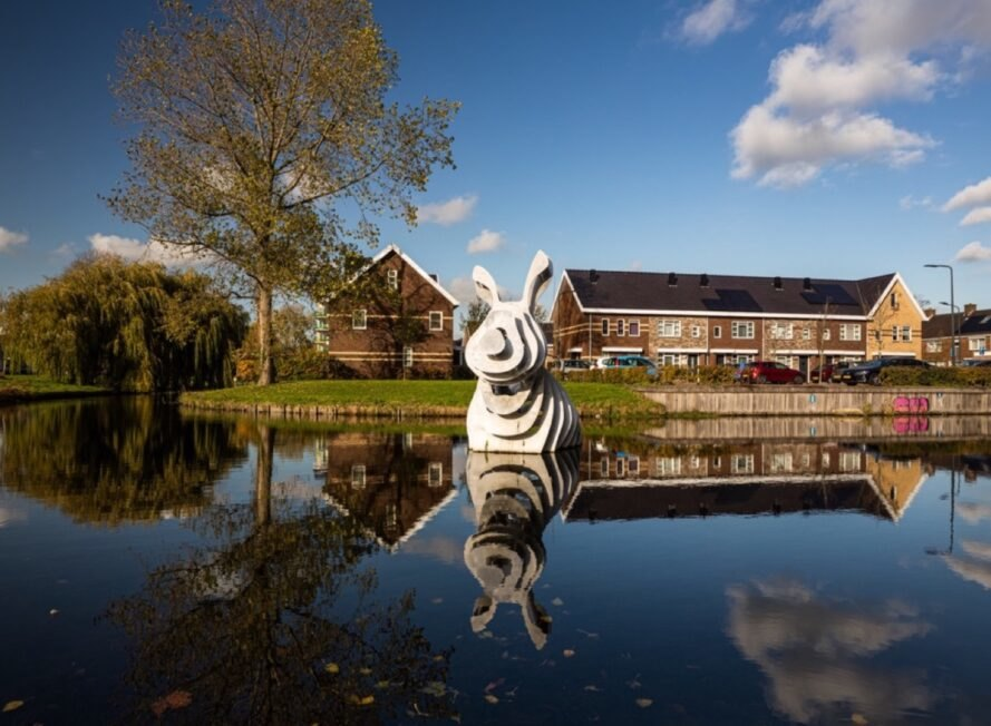 gray 3d-printed rabbit sculpture in a pond