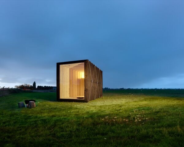 tiny black cabin illuminated in the evening time