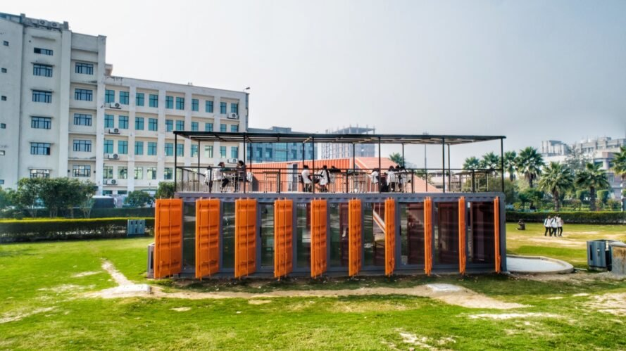 shipping container building with bright orange window louvers