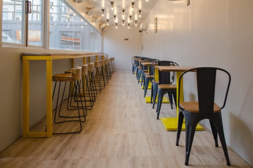 cafe with wood and yellow dining tables and chairs
