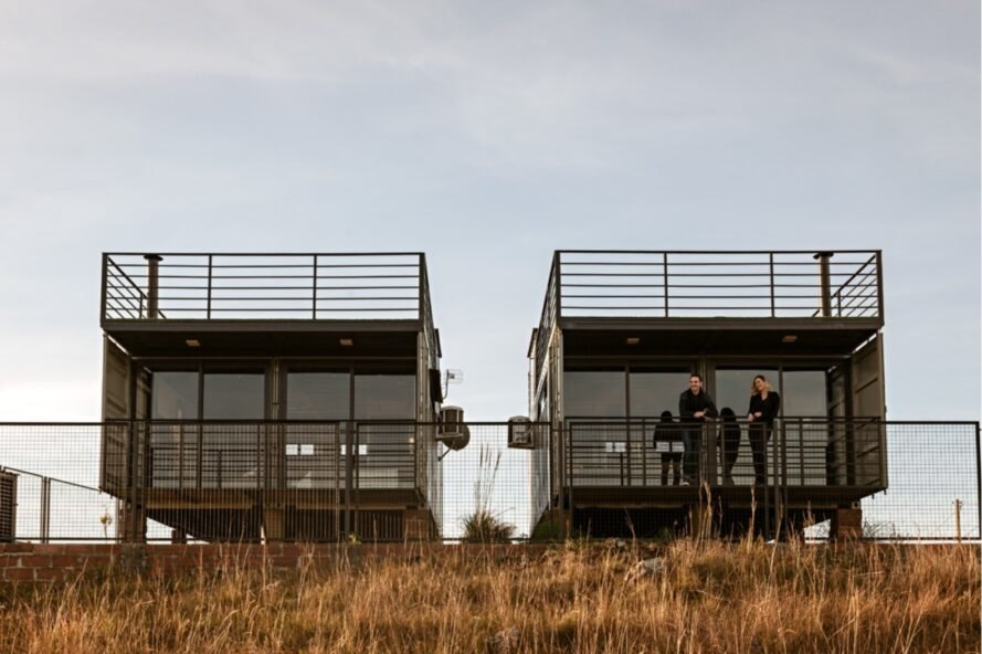 two people on a shipping container home's balcony