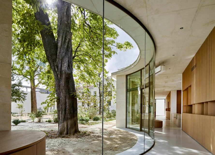a curved glass wall to the left on a hallway. outside are green trees