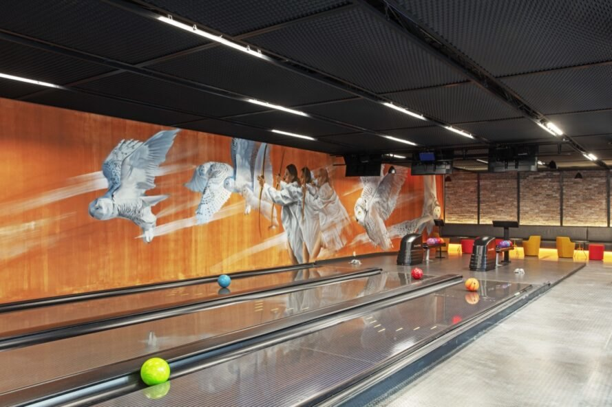 a bowling alley with an orange and white mural on the wall