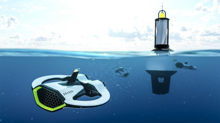 an underwater small white, black and green robot with the word Draper on it, from the front. in the background is another drone and docking station