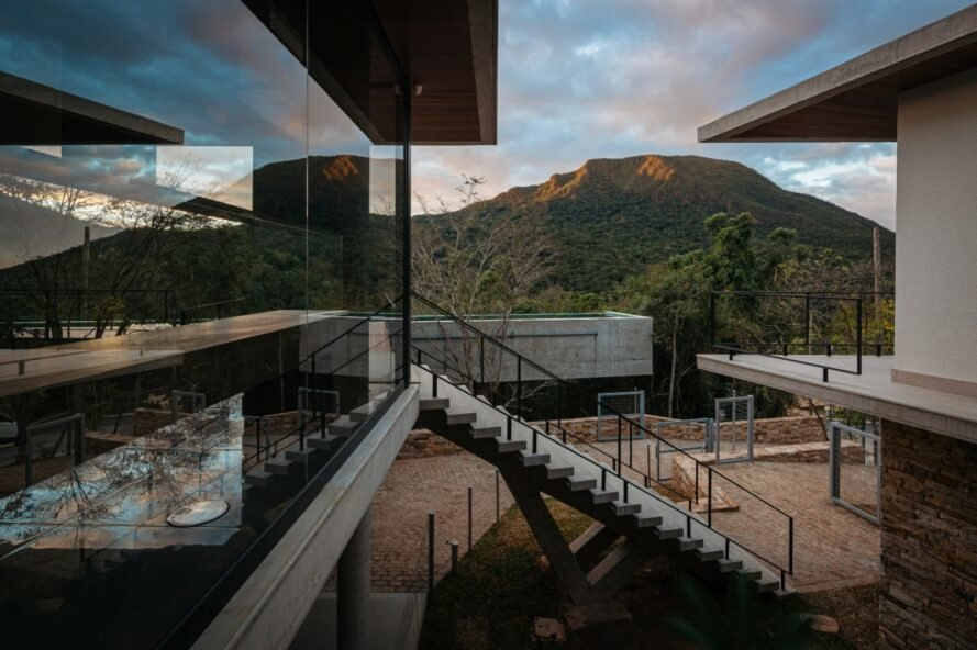 home with large wall of glass and white staircase and mountain in the background