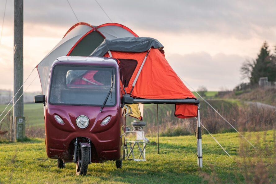 Little red vehicle with an orange camper on top