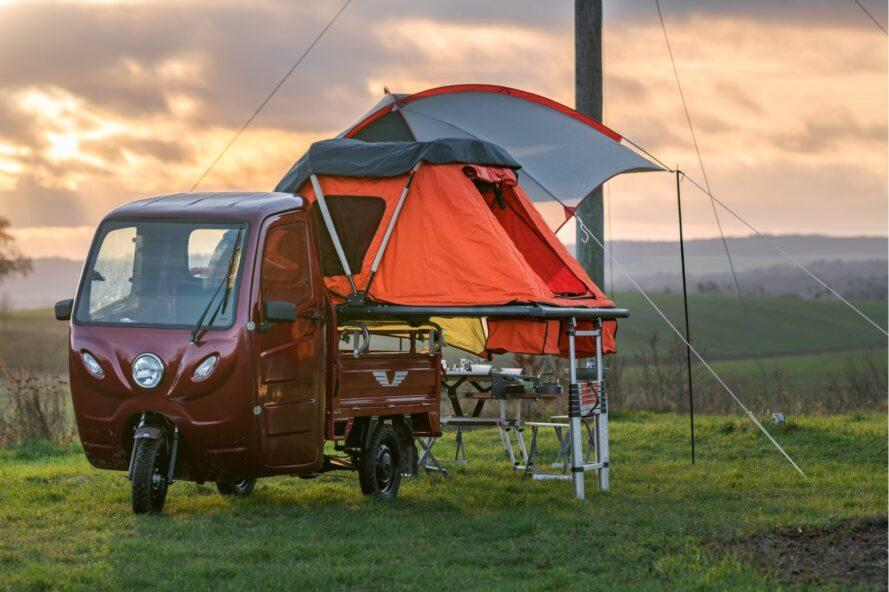red, three-wheeled camper with attached orange tent