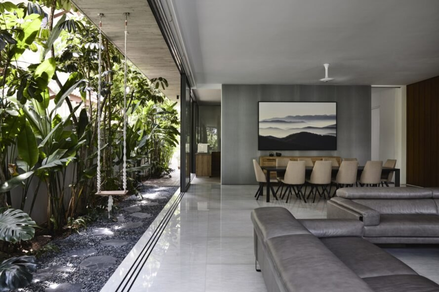 open-plan living room with gray sofa and a wall open to the outdoors