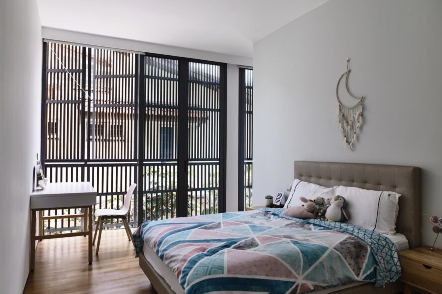 multicolored bed in large white room with windows covered by timber slats