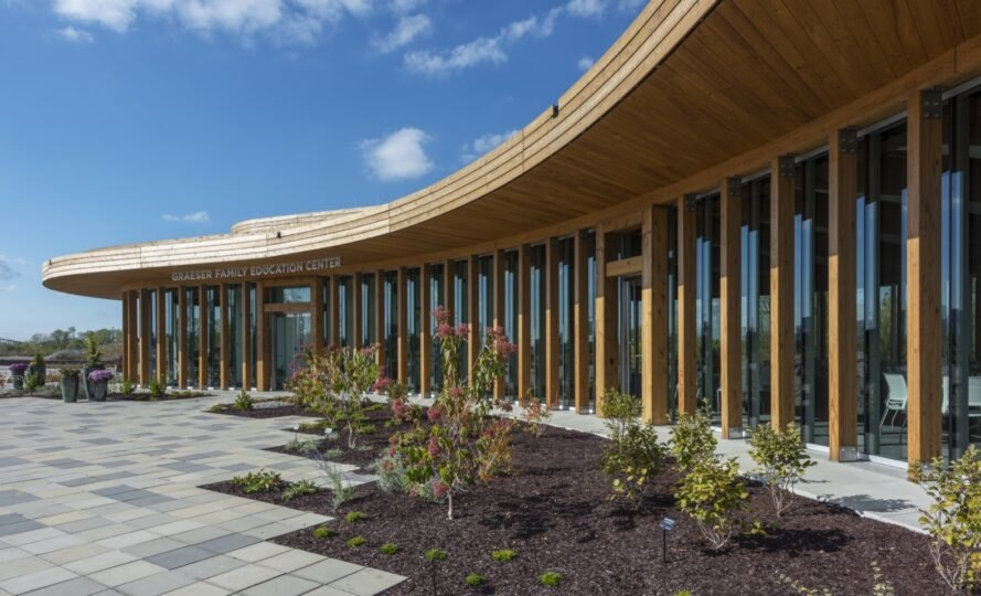 fresh landscaping and plants in front of curved wood building