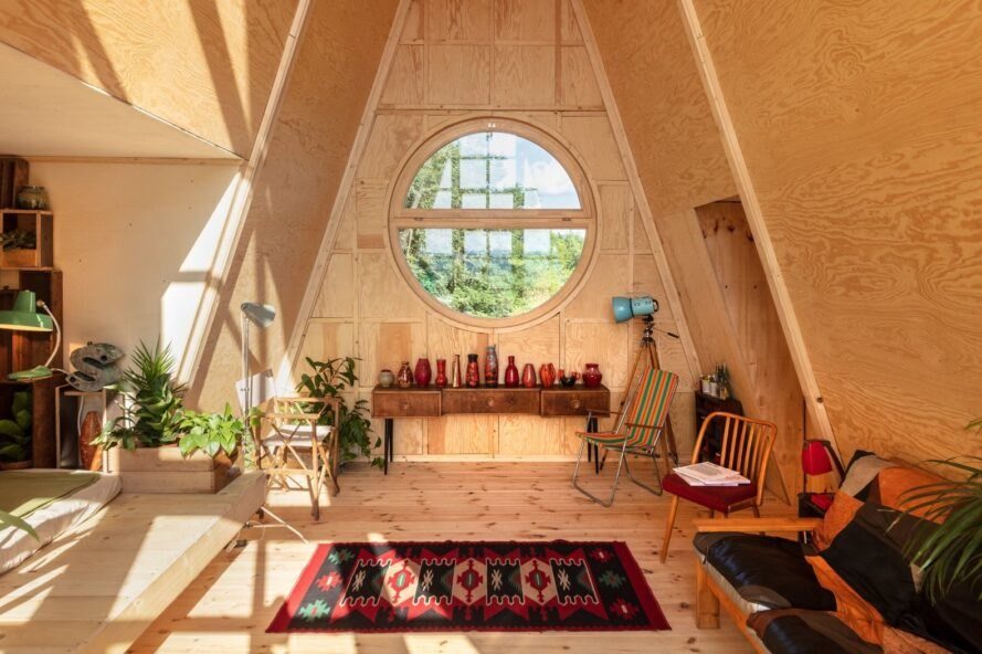 wood cabin with round window, red rug and minimal furniture