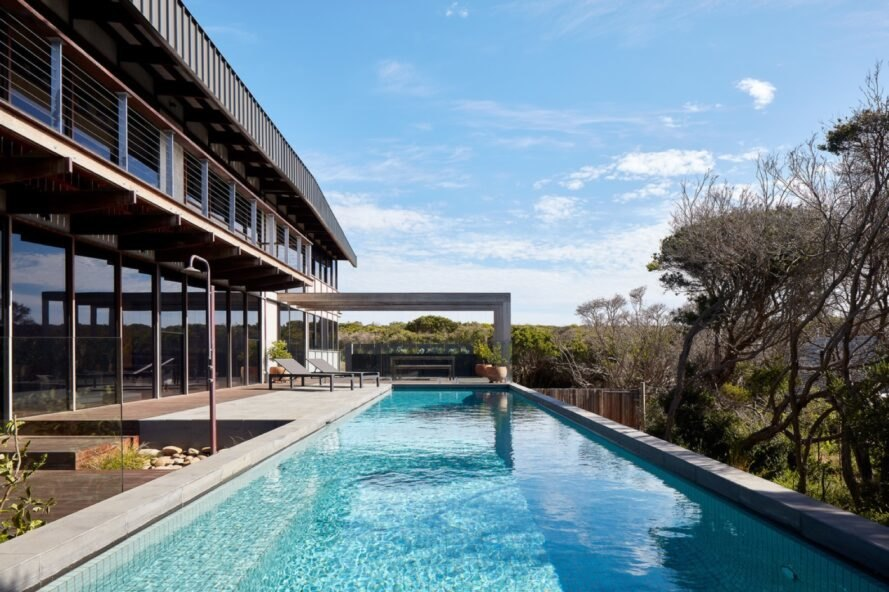 two-story home with deck and large rectangular pool