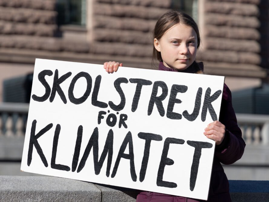 "Greta Thunberg demonstrating in Stockholm on Fridays. Holding a sign that says ""School strike for Climate"""