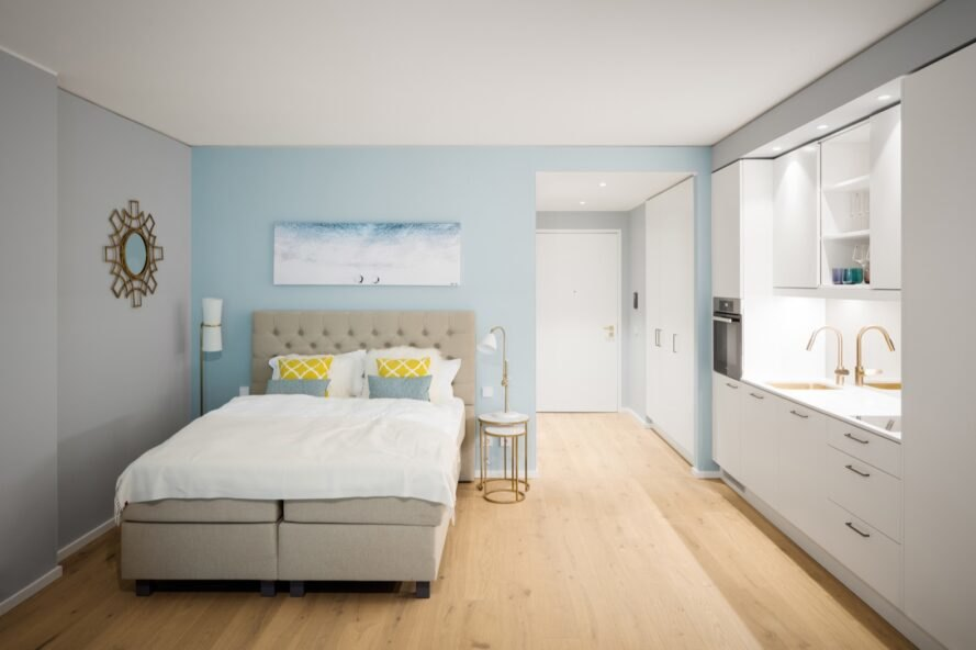 white and light blue bedroom with a gray tufted headboard and large windows
