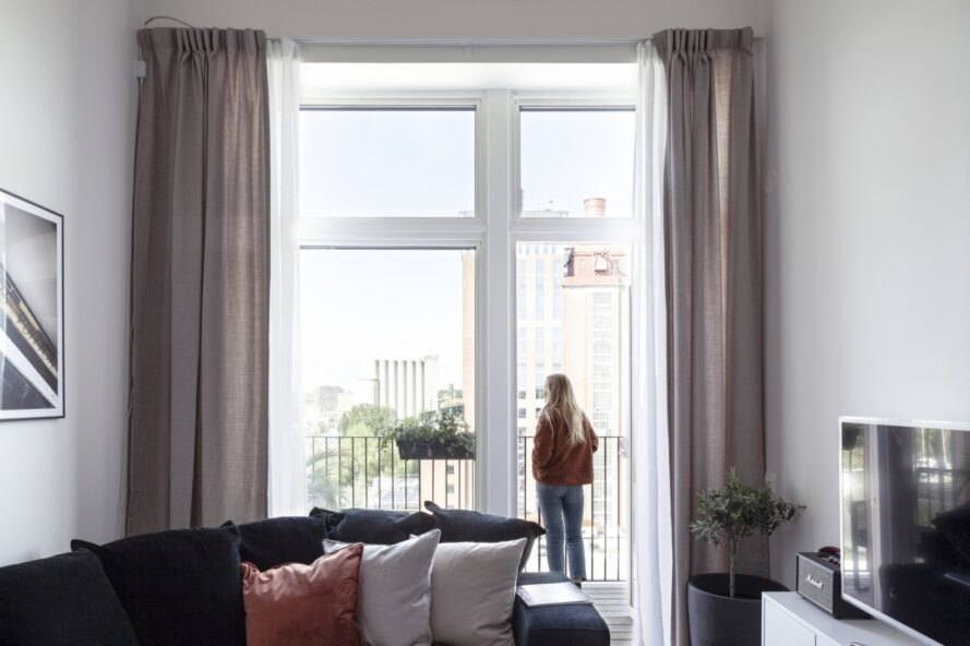 person standing beside full-height window in an apartment