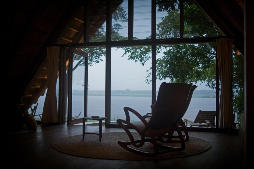 a quiet seating area with single chair looking out over a river