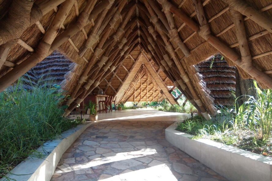 a winding walkway covered in thatched roof